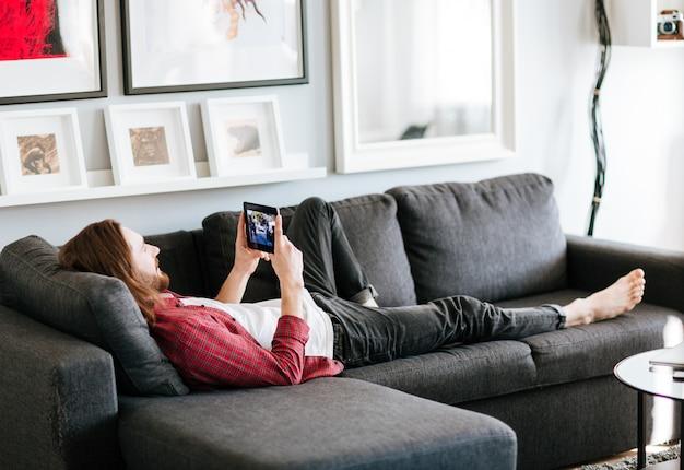 Ontspannen man liggend op de bank en thuis video kijken