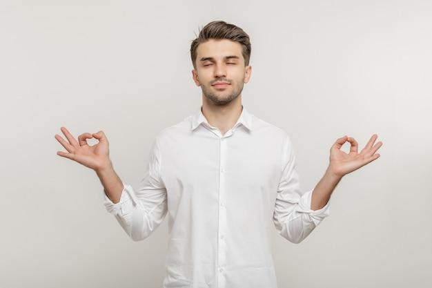 Ontspannen man met gesloten ogen met meditatie op witte achtergrond