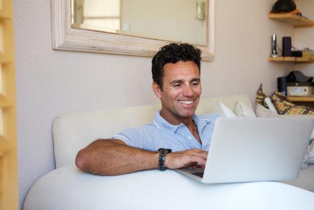 Ontspannen man van middelbare leeftijd lachend met laptop thuis