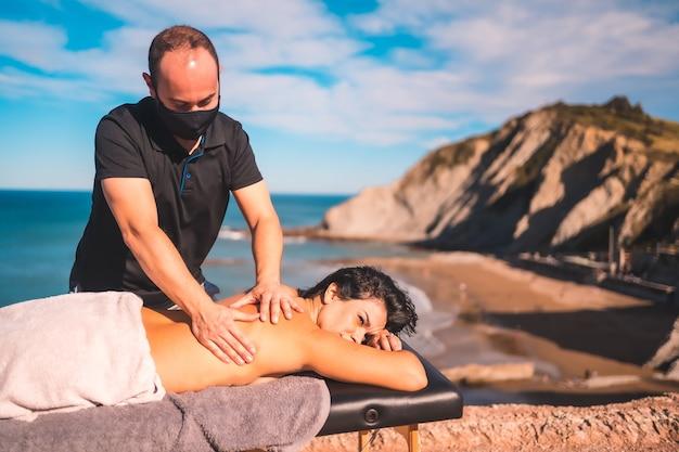 Ontspannen meisje in de massage aan de kust bij de zee, masseuse met gezichtsmasker in de coronavirus-pandemie