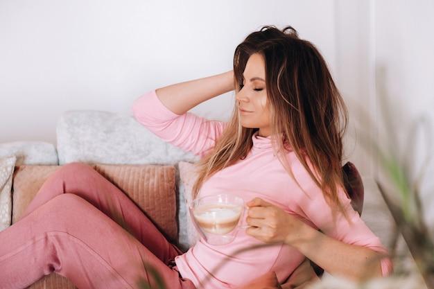 Ontspannen meisje in de ochtend in pyjama thuis koffie drinken. innerlijke vrede. het meisje zit comfortabel op de bank en drinkt koffie terwijl ze over iets droomt