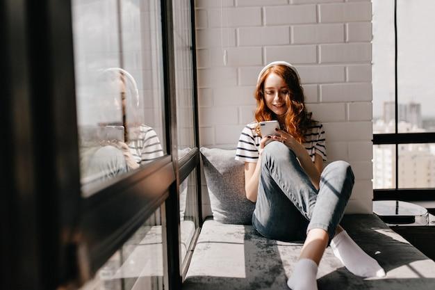 Ontspannen meisje in spijkerbroek zittend op de vensterbank. prachtige gemberdame die in hoofdtelefoons telefoon houdt.
