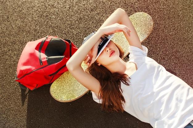 Ontspannen meisje met skateboard en rode rugzak