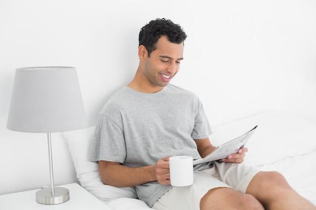 Ontspannen mens met krant en koffiekop in bed