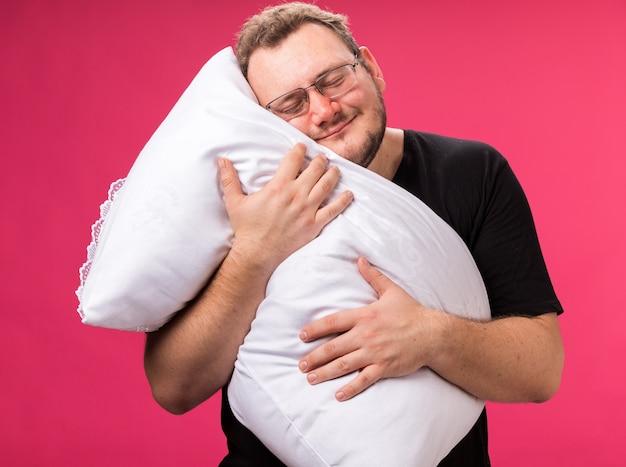 Ontspannen met gesloten ogen zieke man van middelbare leeftijd omhelsd kussen geïsoleerd op roze muur