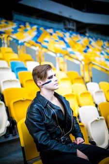 Ontspannen mode voor mannen in leren jas poseren zittend in het stadion