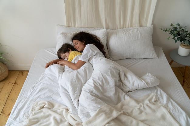 Ontspannen moeder en zoon slapen samen knuffelend kind kwam 's nachts naar bed van moeder bang met een slechte droom