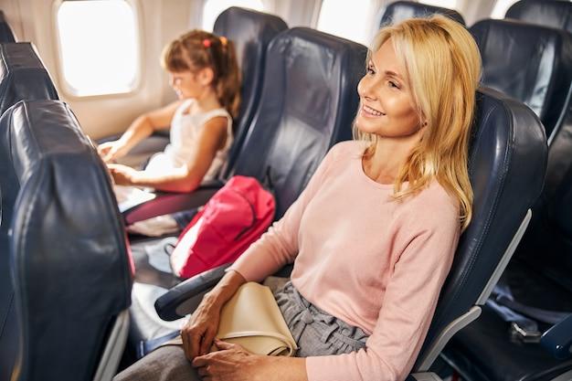 Ontspannen moeder rustend op een vliegtuigstoel