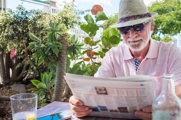 Ontspannen momenten voor een senior gepensioneerde man die in de tuin een krant zit te lezen. tropische planten en zonnige dag