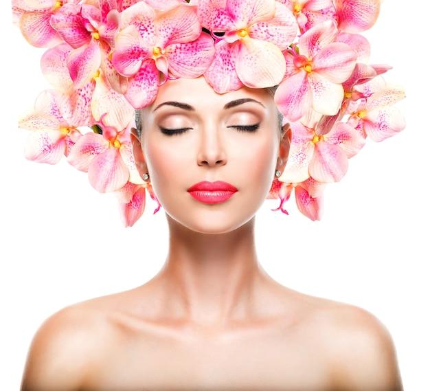 Ontspannen mooi gezicht van een jong meisje met een heldere huid en roze orchideeën. schoonheidsbehandeling concept