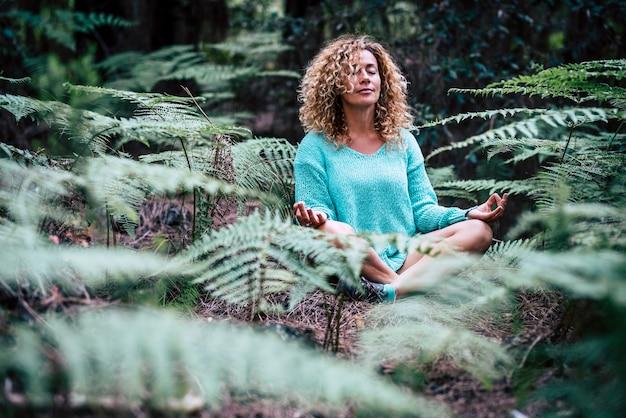 Ontspannen mooie dame meditatie zittend in het midden van de natuur plant buiten