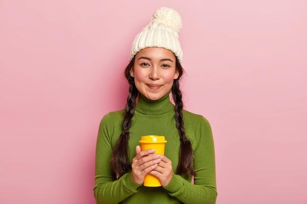 Ontspannen mooie donkerharige vrouw met twee pigtails, houdt afhaalkoffie, verwarmt tijdens de winterdag met warme drank, draagt witte hoed en groene coltrui