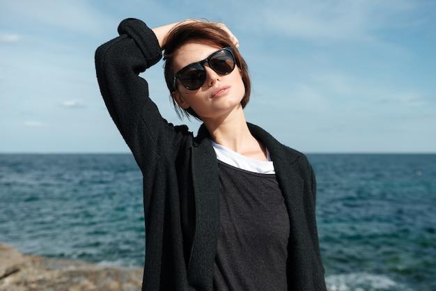 Ontspannen mooie jonge vrouw in zonnebril en zwarte jas staande aan de kust