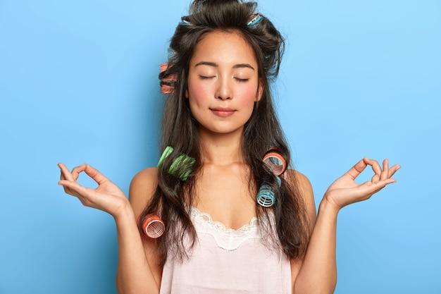Ontspannen mooie jonge vrouw poseren met haarkrulspelden