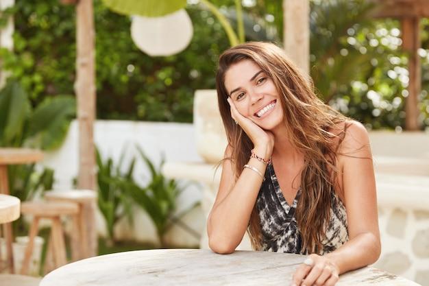 Ontspannen mooie vrolijke vrouw met aantrekkelijke uitstraling, zit in cafetaria, recreëert in tropisch land, gekleed in zomerkleding, heeft een verrukkelijke blik.