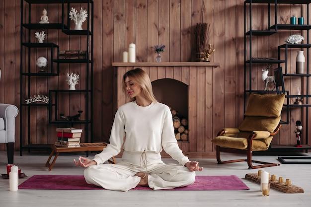 Ontspannen mooie vrouw met blond haar gaat 's ochtends mediteren