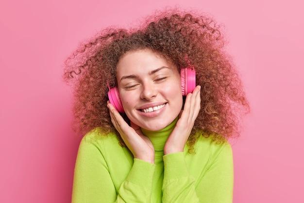 Ontspannen mooie vrouw met krullend haar houdt handen op stereo hoofdtelefoon sluit ogen geniet van favoriete muziek glimlacht zachtjes gekleed in casual kleding geïsoleerd over roze muur. jeugd levensstijl