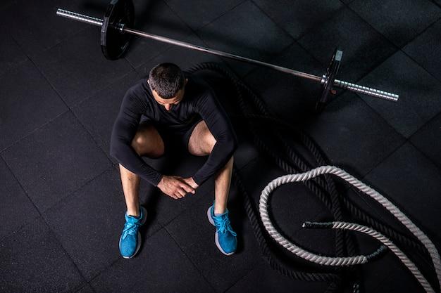 Ontspannen na de training. bovenaanzicht van bebaarde jonge man wegkijken zittend op oefeningsmat op sportschool.