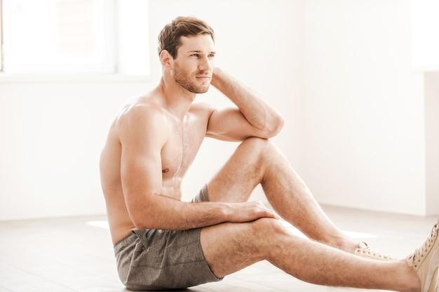Ontspannen na de training. doordachte jonge shirtloze man in korte broek zittend op de vloer