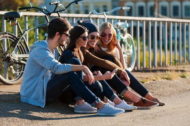 Ontspannen na een dag rijden. groep jonge lachende mensen die zich aan elkaar hechten en naar een smartphone kijken terwijl ze buiten zitten samen met fietsen op de achtergrond
