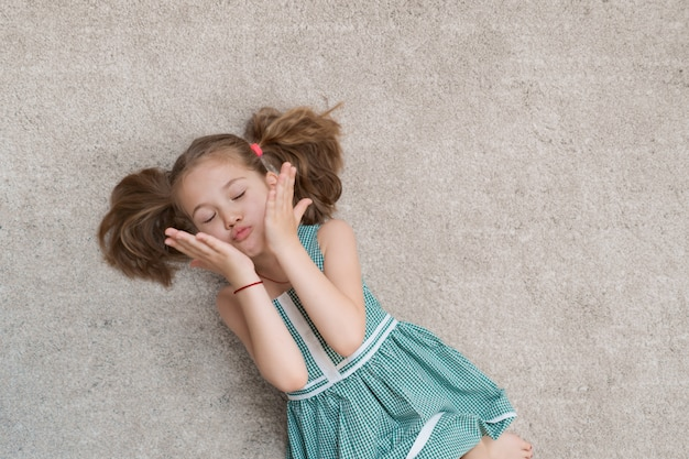 Ontspannen op de vloer liggen binnen en meisje die glimlachen