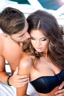 Ontspannen op het strand, vrouw met moderne zwarte top, bronzen zachte huid, make-up op haar mooie gezicht. tender holding