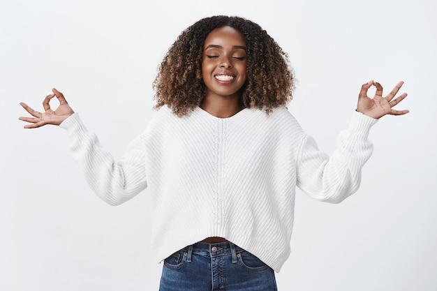 Ontspannen, opgeluchte afro-amerikaanse vrouw ademt lucht in die lacht opgetogen mediteert met gesloten ogen, toont lichtbollen, nirvana-gebaar, lotus pose witte muur