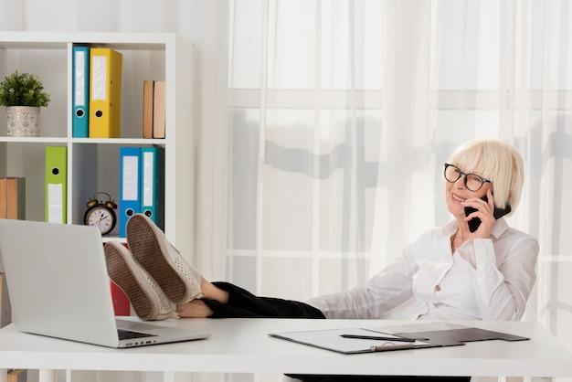 Ontspannen oude vrouw die met oogglazen op haar bureau zit