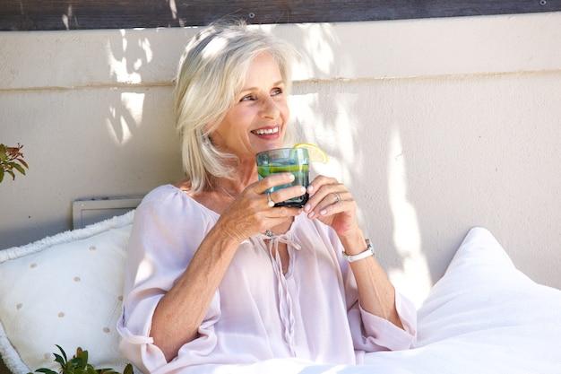 Ontspannen oudere vrouw buiten het drinken van thee met citroen