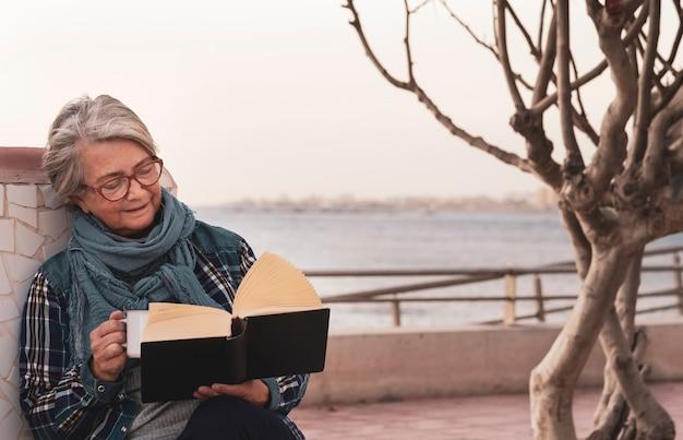 Ontspannen pensioen voor een senior vrouw die geniet van de zonsondergang terwijl ze een boek leest dat in de buurt van het strand zit - horizon op het water.