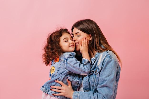 Ontspannen preteen meisje omarmen met moeder. winsome jonge moeder kussen dochter op roze achtergrond.