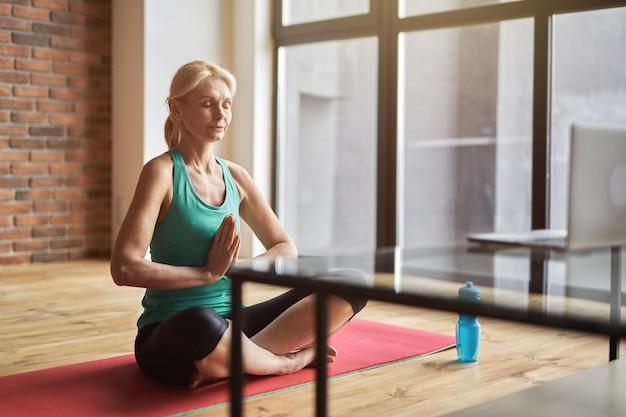 Ontspannen rijpe blonde vrouw die yoga beoefent, mediteert met gesloten ogen op de vloer en doet