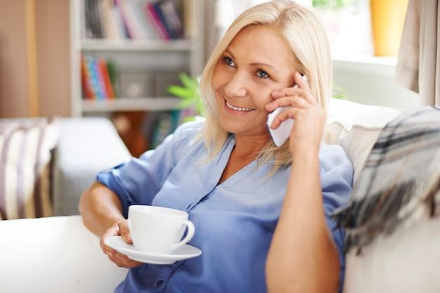 Ontspannen rijpe vrouw die van gesprek op mobiele telefoon geniet