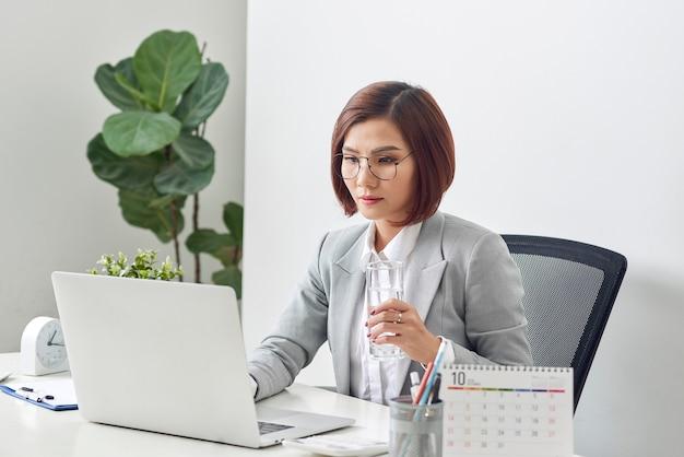 Ontspannen rijpe zakenvrouw glas water houden en bezig met haar laptop op kantoor