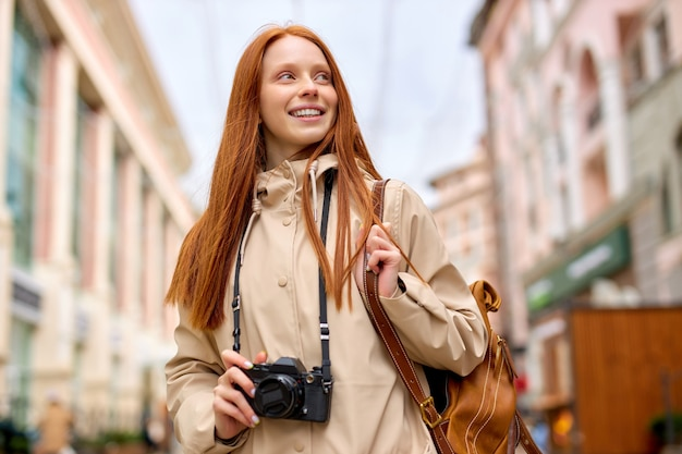 Ontspannen roodharige vrouw reiziger met warme glimlach foto nemen op film retro camera tijdens het wandelen in stedelijke stad, portret van trendy vriendelijke dame in vrijetijdskleding met rugzak bij koud lenteweer