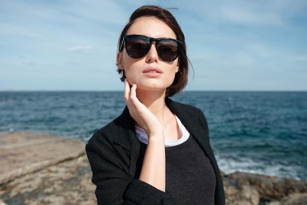 Ontspannen schattige jonge vrouw in zonnebril aan de kust