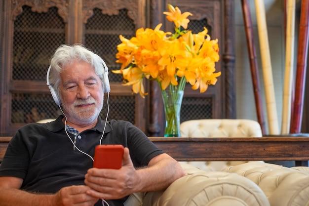 Ontspannen senior man met behulp van mobiele telefoon met koptelefoon. gepensioneerde witharig zit binnen
