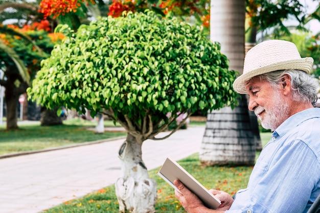Ontspannen senior man met witte baard glimlacht zittend in het park een boek te lezen