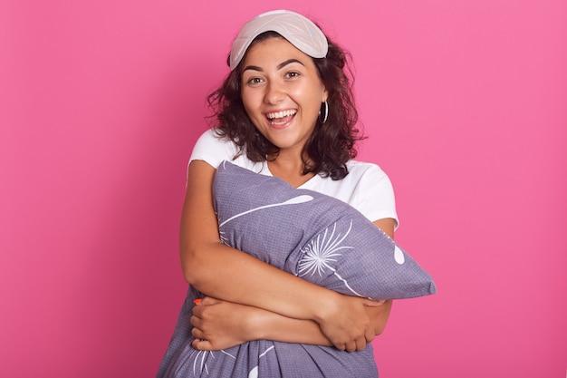 Ontspannen sensuele gelukkige jonge vrouw die grijs hoofdkussen koestert, dat camera met charmante glimlach bekijkt