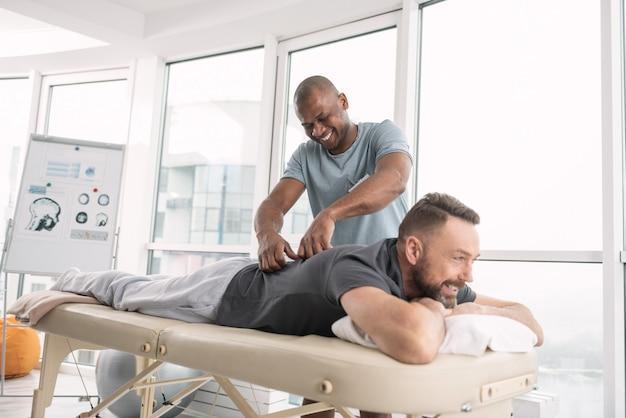 Ontspannen sfeer. gelukkig opgetogen man die lacht terwijl hij een rugmassage voor zijn patiënt doet