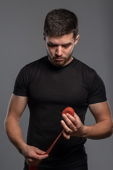 Ontspannen sportieve man die bokstape oprolt na een bokstraining