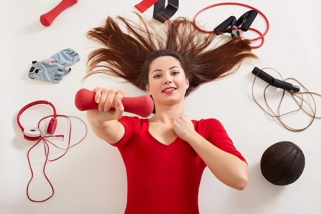 Ontspannen sportvrouw omringd met koptelefoon, rolcontainer, fitnesshandschoenen, elastische banden, expander, medbal, dame in rode outfit liggend op wit oppervlak, met rode halter in de hand.