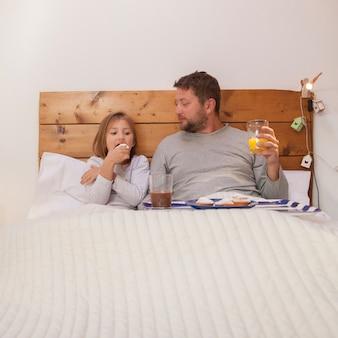 Ontspannen vader en dochter hebben ontbijt in bed