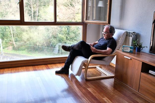 Ontspannen volwassen man lezen op tablet in de woonkamer thuis naast raam