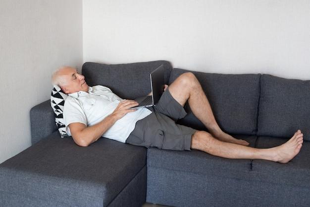 Ontspannen volwassen man thuis werken met laptop, liggend op de bank