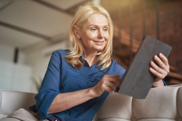 Ontspannen volwassen vrouw scrollen nieuwsfeed met behulp van digitale tablet-pc ontspannen op een bank thuis in