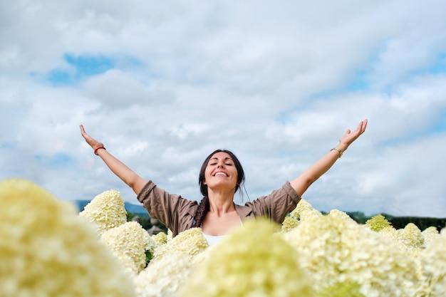 Ontspannen volwassen vrouwtje met gesloten ogen in een veld met witte hortensia's die armen optillen naar de hemel
