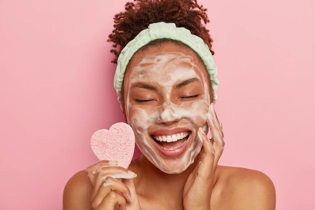 Ontspannen vreugdevolle donkere huid vrouwelijk model wast gezicht met zeepbellen, geniet van verwen sessie, houdt de ogen gesloten van plezier, houdt cosmetische spons vast, geeft om lichaam, staat naakt binnen