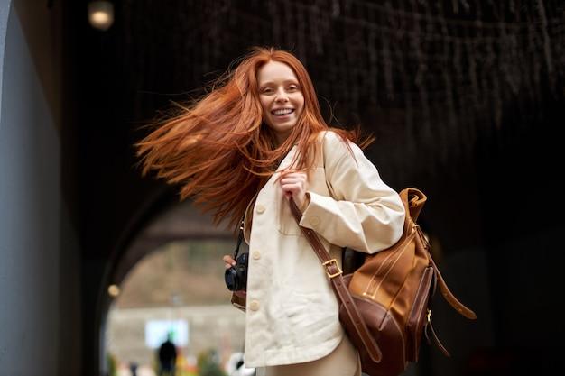 Ontspannen vriendelijke trendy jonge roodharige vrouw met warme glimlach wandelen, genietend