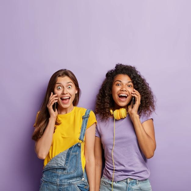 Ontspannen vriendinnen poseren met hun telefoons